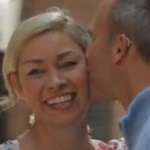 Woman smiling while man with hearing aid kisses her cheek